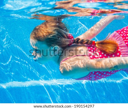 The cute girl swimming underwater and smiling