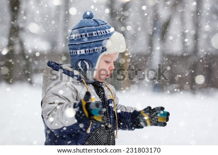 the cute  little boy catches snowflakes in the frosty winter afternoon - stock photo