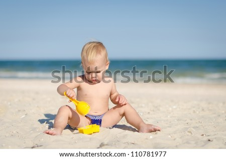 The cute little boy playing toys on the seashore