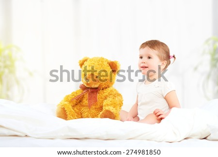the cute little child girl hugging teddy bear in bed - stock photo