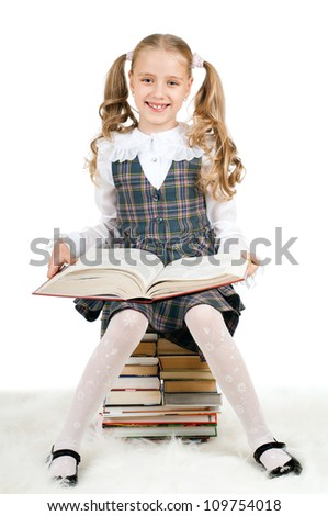 the cute little teen girl sit and smile,  read big textbook, on white background, isolated - stock photo
