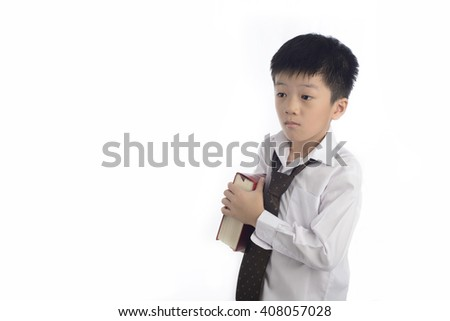 The cute smart chinese schoolboy boy holds a heavy book