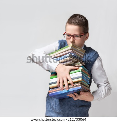 The cute smart schoolboy teenager in a glasses holds a heavy stack of books. - stock photo