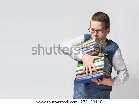 The cute smart schoolboy teenager in a glasses holds a heavy stack of books on the horizontal background - stock photo