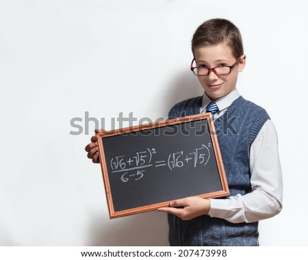 The cute smart schoolboy teenager in a glasses shows the black chalkboard with the mathematical equation - stock photo