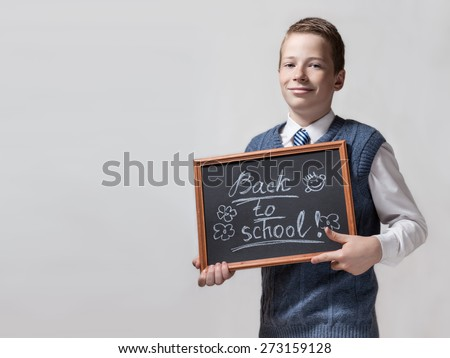 The cute smart smiling schoolboy teenager shows the black chalkboard with the inscription - back to school,on the horizontal background - stock photo