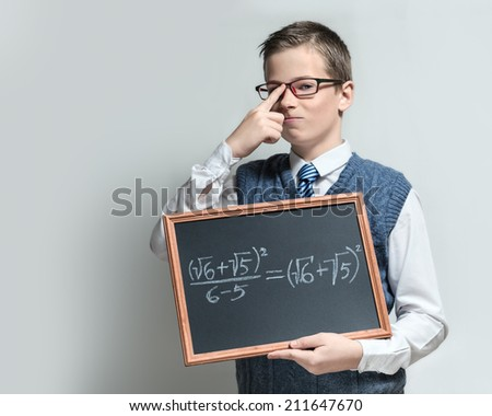 The cute smart swagger schoolboy teenager in a glasses shows the black chalkboard with the mathematical equation - stock photo