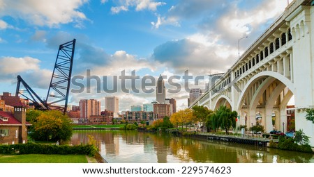 The Cuyahoga River bends past downtown Cleveland by the Veterans Memorial Bridge with old lift bridge at left
