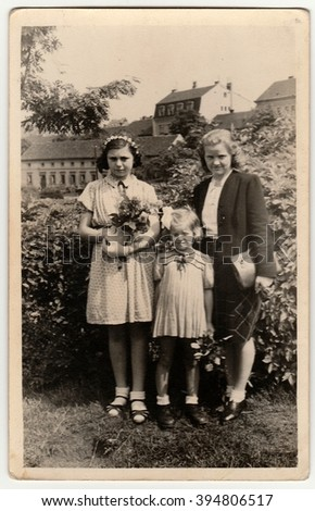 THE CZECHOSLOVAK  REPUBLIC - 1946: Vintage photo shows girls with mother after confirmation ceremony. Black & white antique photography.
