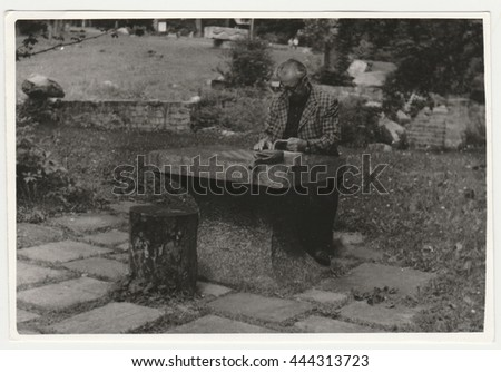 THE CZECHOSLOVAK SOCIALIST REPUBLIC - CIRCA 1970s: Retro photo shows man sits at the stone table outside. Black & white vintage photography.