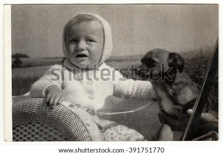 THE CZECHOSLOVAK SOCIALIST REPUBLIC - CIRCA 1980s: Vintage photo shows baby boy with dog outdoors. Antique black & white photo.