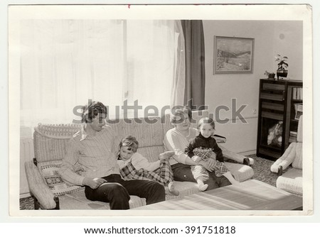 THE CZECHOSLOVAK SOCIALIST REPUBLIC - CIRCA 1980s: Vintage photo shows parents with their children in the living room. Antique black & white photo.