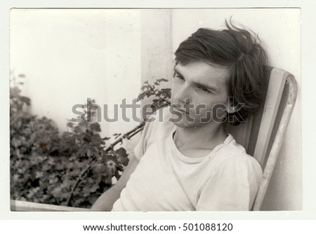 THE CZECHOSLOVAK  SOCIALIST  REPUBLIC - JULY 1981: Vintage photo shows a teenager boy sits on camping chair outdoors.  Retro black & white  photography.