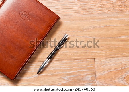 The daily log and the handle on a wooden background The brown daily log and the black handle against a wooden covering. The floor wooden covering painted by a protective varnish. - stock photo
