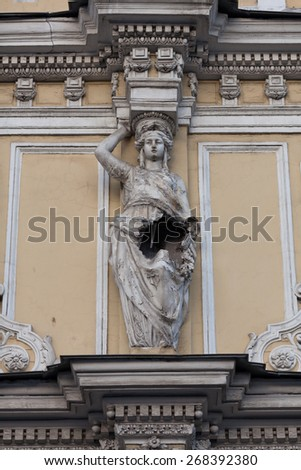 The damaged sculpture Caryatid on the facade of an old house in St. Petersburg, Russia - stock photo