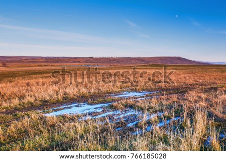 The dark blue sky above the horizon, the first autumn frost in the puddles of a dirt road. The moon is high in the sky. It's getting dark. Slopes of hills in the distance, a strip of river water.