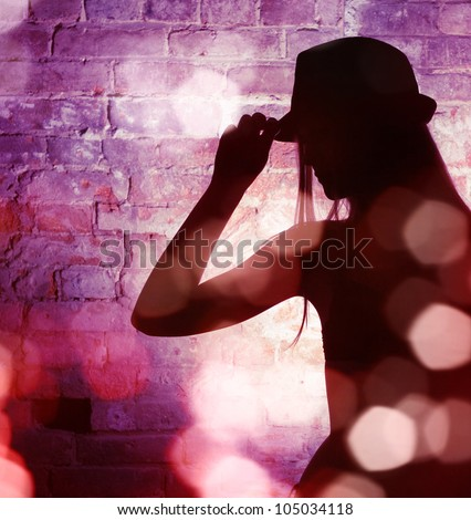 The dark silhouette of an elegant woman in a man's hat against a brick wall. Night club. - stock photo