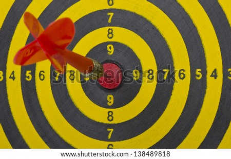 the dart hitting the middle of dartboard, close up - stock photo