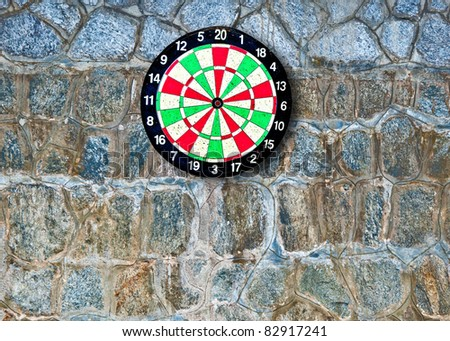 The Dartboard on rock wall background