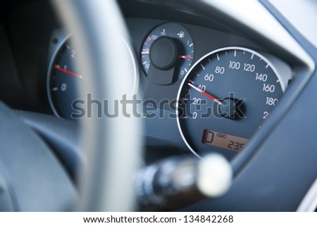 The dashboard of car going 40, within speed limits. Very shallow depth of field. - stock photo