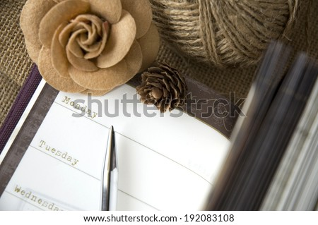 the day on planner page open with flower and pen - stock photo