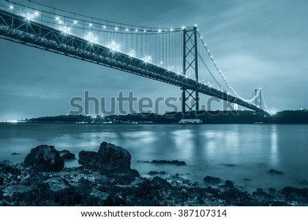 The 25 de Abril bridge over Tagus river and big Christ monument in Lisbon, Portugal, black and white blue toned - stock photo