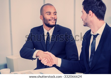 The deal confirmed by handshake. Two successful businessman sitting at the table looking at each other shaking hands - stock photo