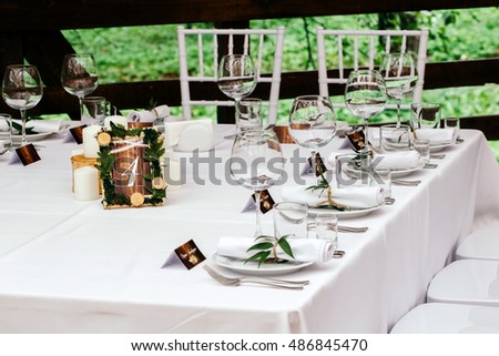 The decor at the wedding. Room table in a beautiful wooden frame, stands on a white tablecloth decorated with leaves and cut down.