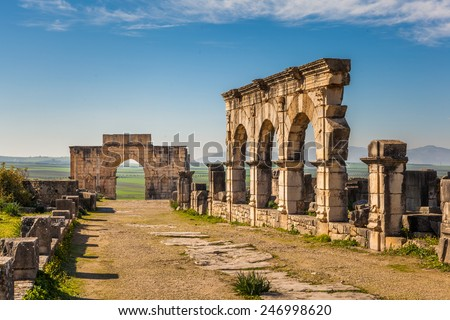 The Decumanus Maximus with the Hercules Works House and the Triumphal Arch, Volubilis, Morocco - stock photo
