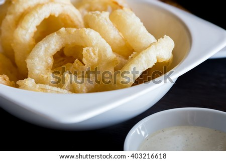 The deep fried onion rings with white dipping sauce, one of the world favorite junk food with trans-fat. - stock photo