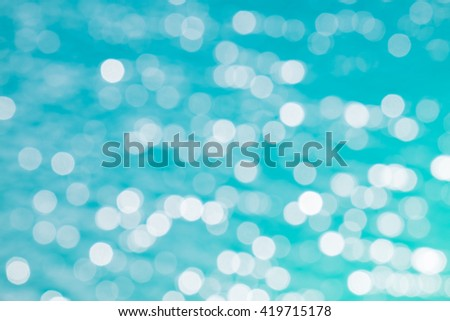 The Defocused Of Water surface with waves glittering in the sun. Out of focus bokeh of sun glares reflected in dark color - stock photo