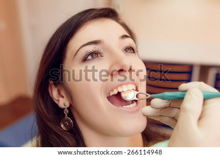 The dentist treats teeth beautiful girl - stock photo