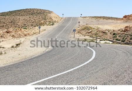 The desert winding road near the Sahara desert. - stock photo