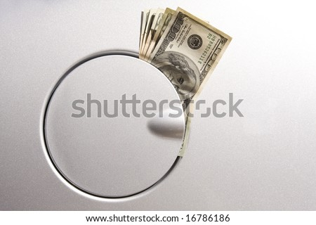 the detail of a gas tank with dollar notes inside - stock photo