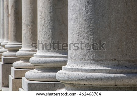 The detailed view of the peristyle. Ancient colonnade close. Series of white columns.