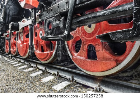 The details of drive mechanism and red wheels of an old soviet steam locomotive - stock photo
