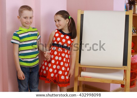 the development of emotional intelligence. child psychology. girl and boy depict different emotions. against the background of the drawing board. love between a boy and a girl - stock photo