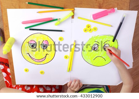the development of emotional intelligence. child psychology. the girl and the boy draw happy and sad emoticons - stock photo