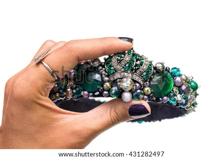 The diadem or tiara with precious green stones isolated in the woman's hand