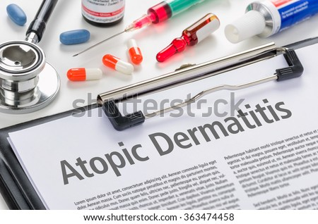 The diagnosis Atopic Dermatitis written on a clipboard - stock photo
