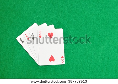 The different suit of the number 2 cards in a deck of cards displayed on a green background