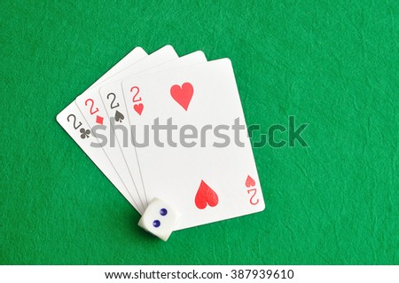 The different suit of the number 2 cards in a deck of cards displayed with a dice  on a green background