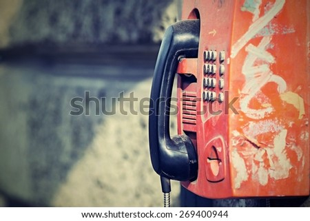 the digital photo with a retro effect the old payphone with receiver is fixed on a gray stone wall with a blank space for the text - stock photo