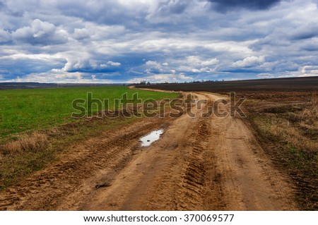 The dirt road between fields. Early spring, nature wakes up after winter. Changeable weather of April.