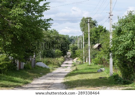 The dirt road in the Ukrainian village. The pillars stand along the road.