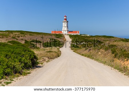 The dirt road leading to the Espichel Cape lighthouse. Built during the 18th century is one of the oldest lighthouses in Portugal and guides boats and ships in the Atlantic Ocean. Sesimbra, Portugal. - stock photo