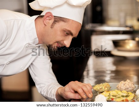The dis is ready to be served. Satisfied male chef. - stock photo