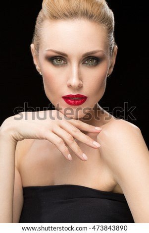 The Diva look. Vertical portrait of a gorgeous beautiful mature blonde woman wearing evening makeup with red lips looking fiercely to the camera with her hand to her chin
