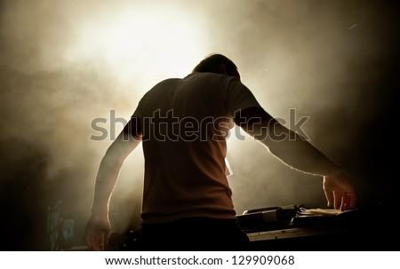 the DJ behind work in night club - stock photo
