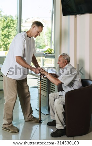 The doctor helping an old man get up from the chair